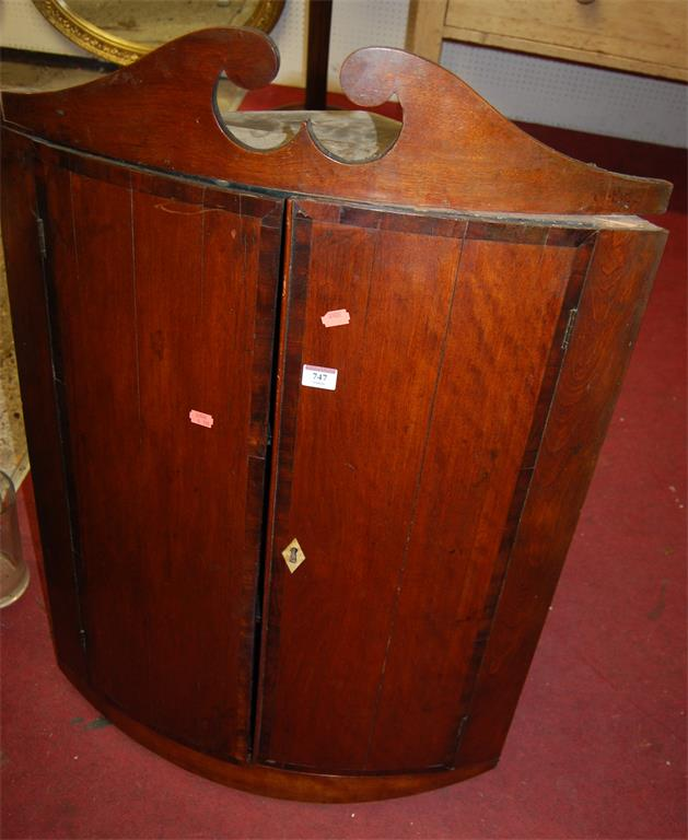 A George III mahogany and crossbanded bowfront double door hanging corner cupboard