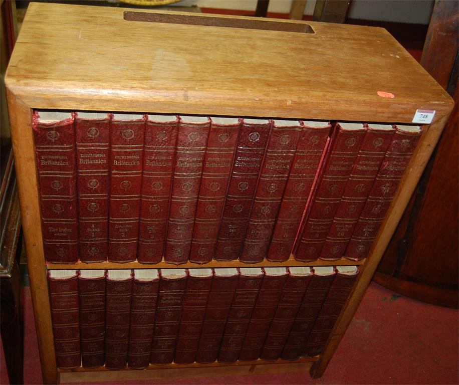 A mid-20th century beech two tier open bookshelf with sundry Encyclopaedia Britannica volumes