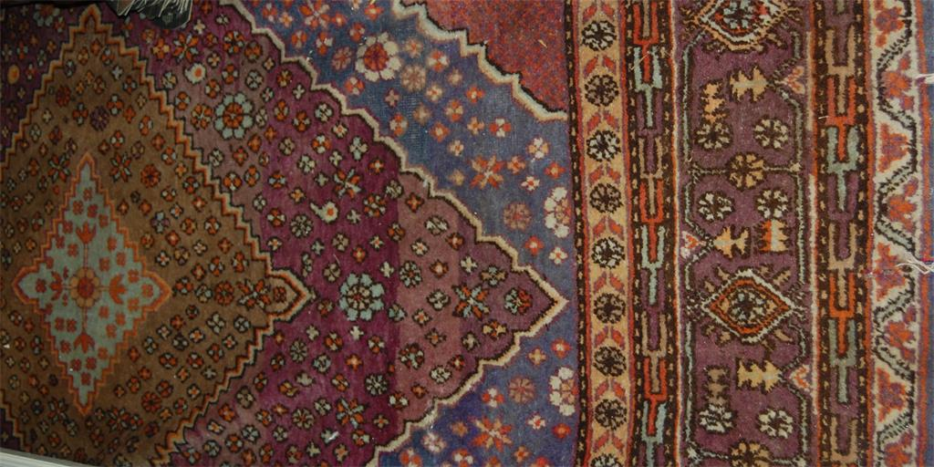 A Persian woollen carpet, the central ground having two large lozenge medallions within multiple trailing borders