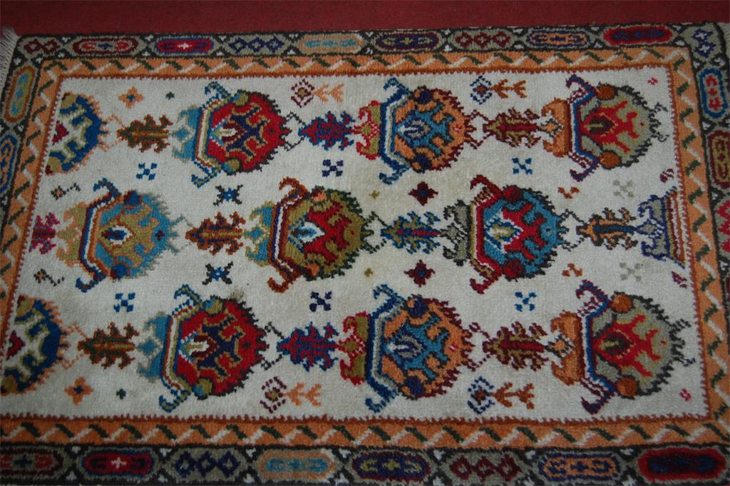 A Persian style cream ground woollen rug