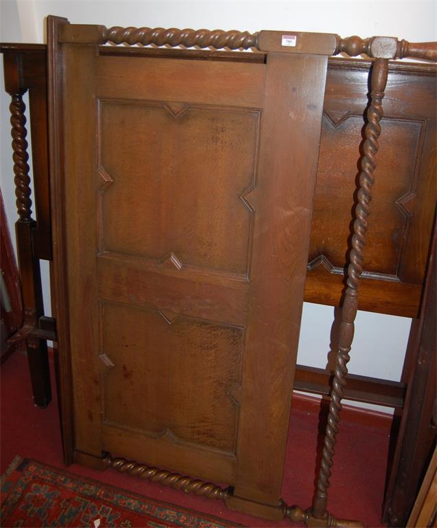 An early 20th century barleytwist oak double bedstead, having iron side-rails