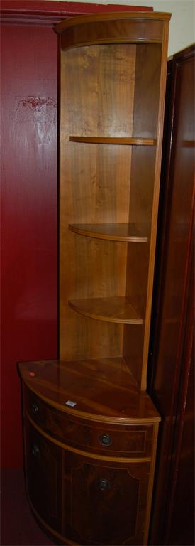 A reproduction yew wood freestanding corner cupboard, having open upper shelves