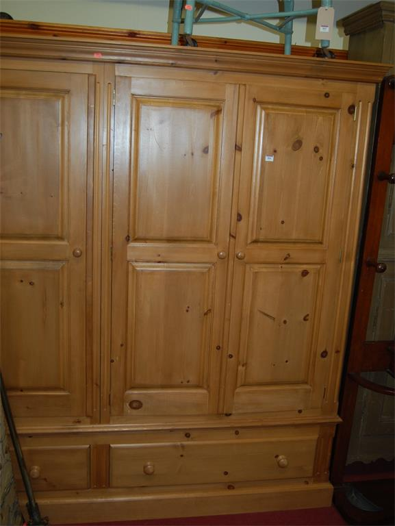 A modern pine three door wardrobe over two lower drawers