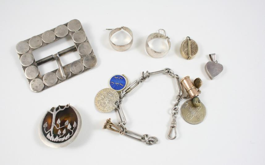 a silver buckle, a pair of silver hoop earrings and various other items