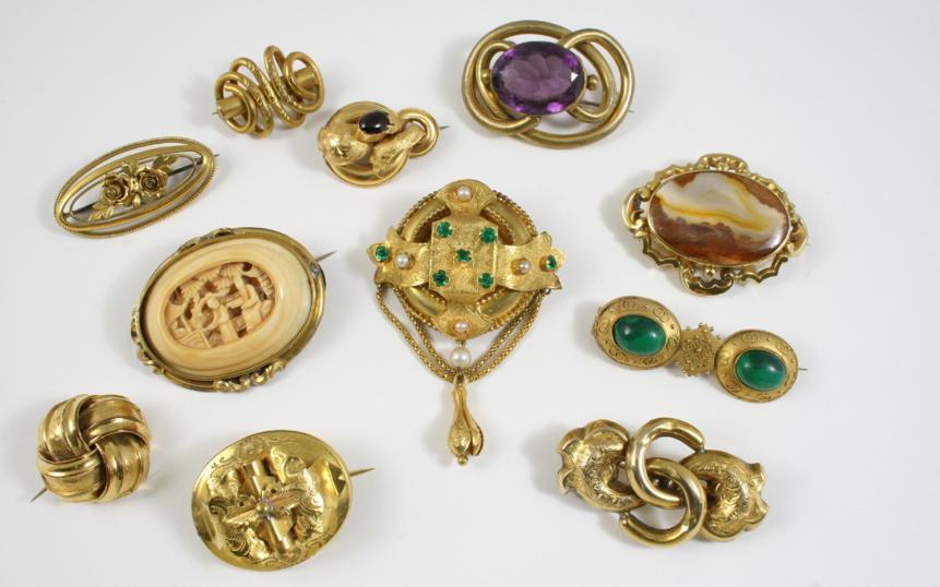 a Victorian gold brooch set with a cabochon garnet