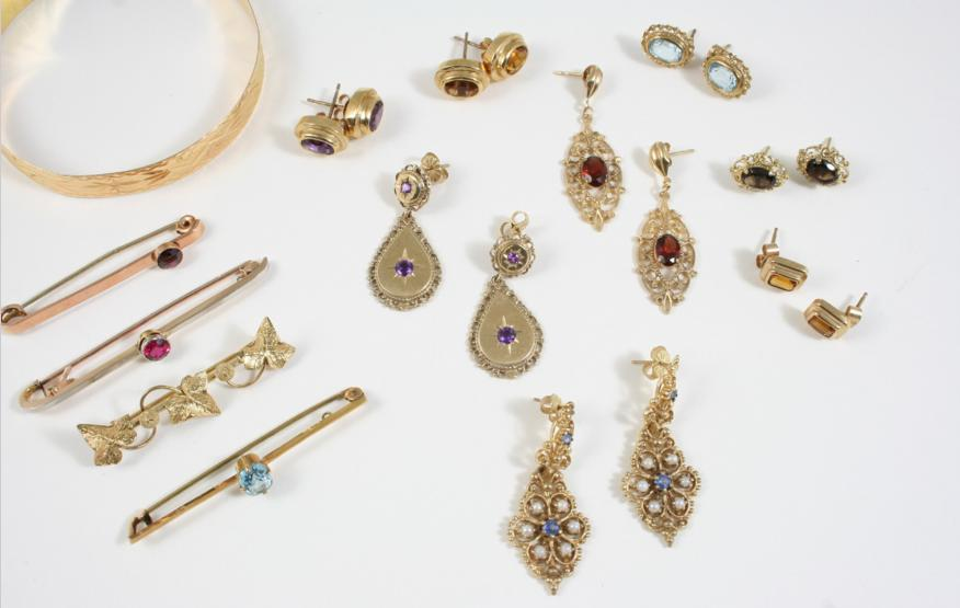 a pair of gold drop earrings set with amethysts