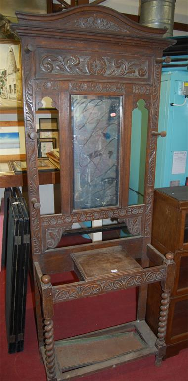 An early 20th century low relief carved oak mirrorback hall-stand