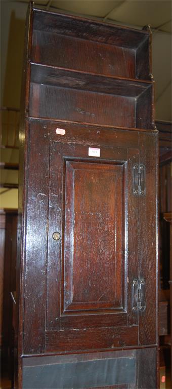 An antique joined oak narrow side cupboard, having stepped upper shelves