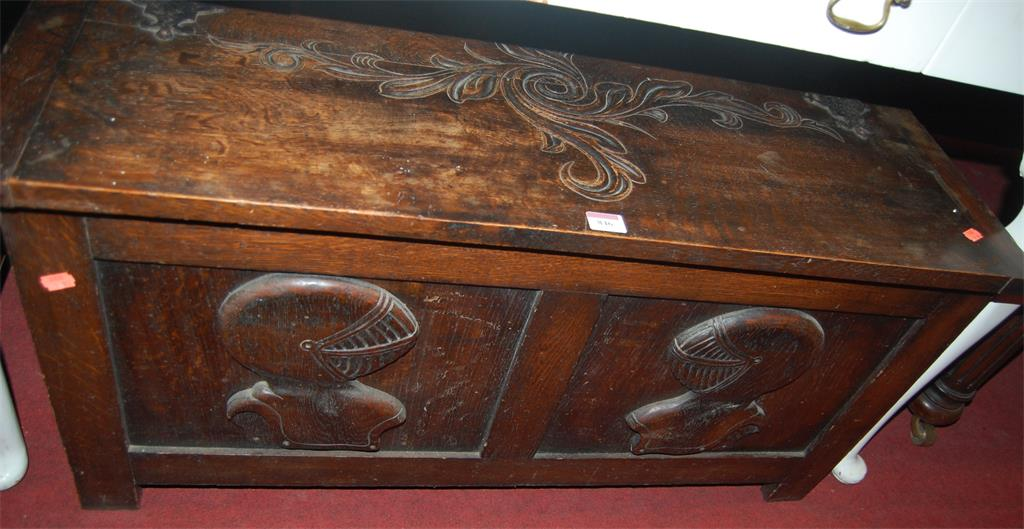 An early 20th century low relief carved oak twin panelled hinge-top blanket box