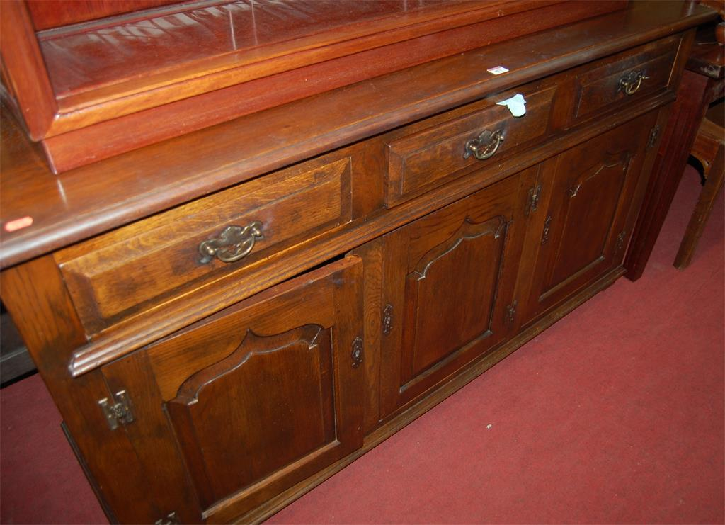 A 17th century style joined oak three door sideboard, having three short upper drawers