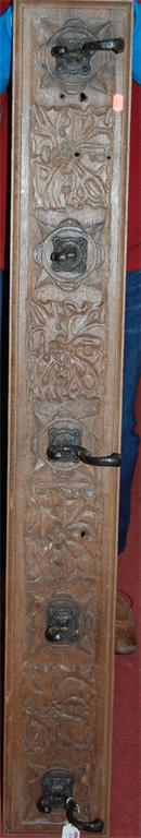 A low relief carved oak and iron mounted set of wall hooks