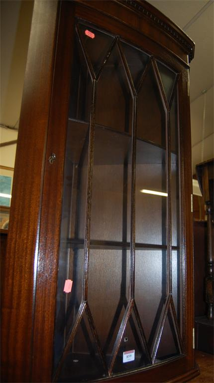 A reproduction mahogany bowfront single door glazed hanging corner cupboard