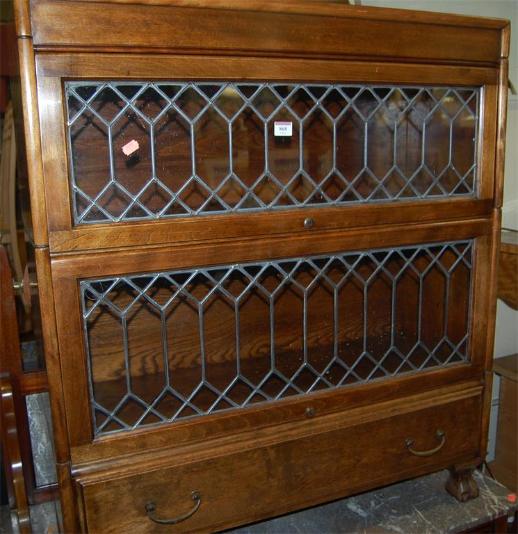 A 1930s walnut lead glazed two tier stacking bookcase, having single long lower drawer