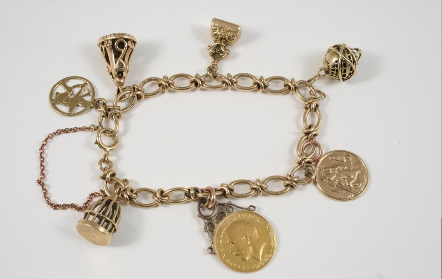 A 9CT. GOLD CHARM BRACELET