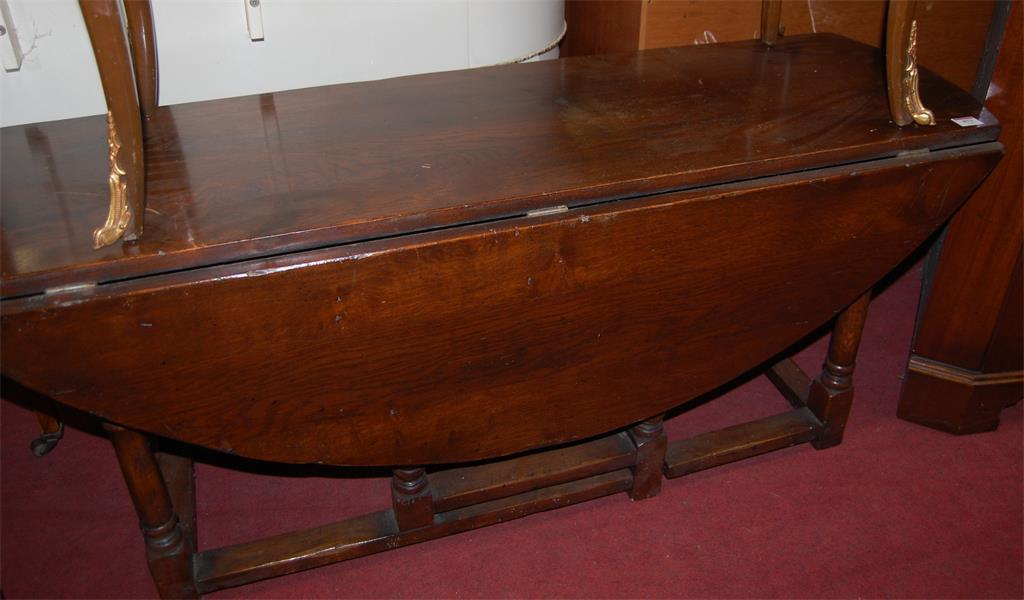 A 17th century style joined oak dropflap occasional table, having gateleg action