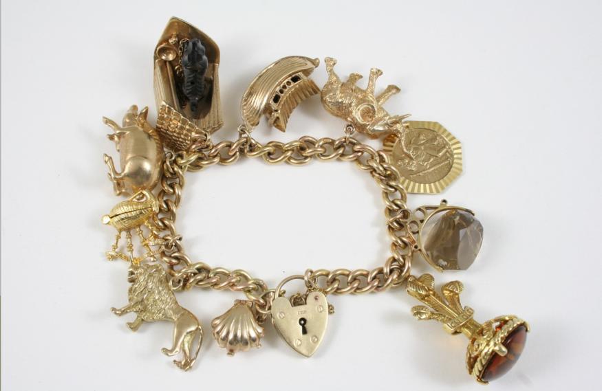 A 9CT. GOLD CURB LINK CHARM BRACELET
