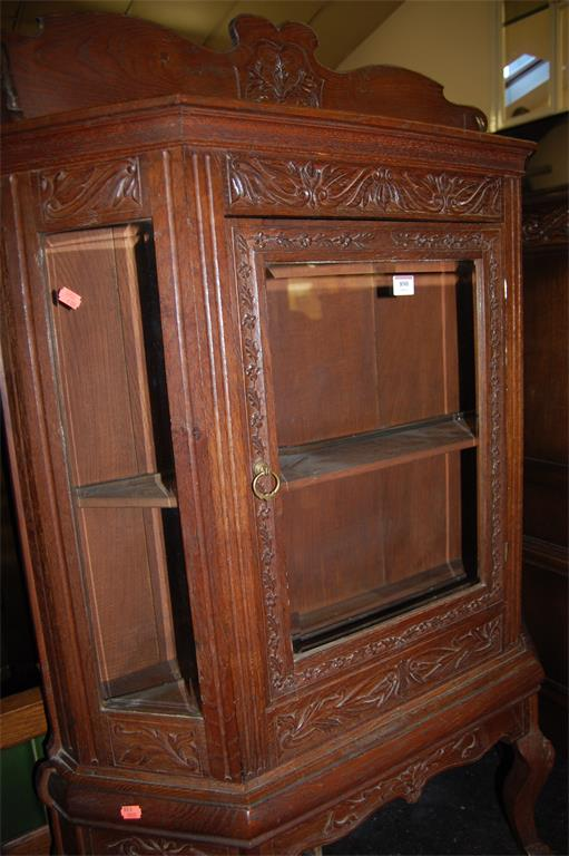 A Continental low relief carved oak ledgeback single door glazed display cabinet of credence form