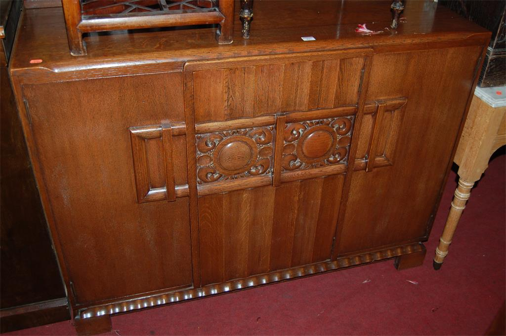 An Art Deco oak three door sideboard, having a fitted centre compartment