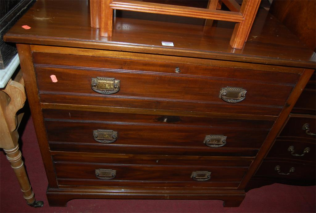 An Edwardian walnut squarefront chest of three long drawers (formally a dressing chest)