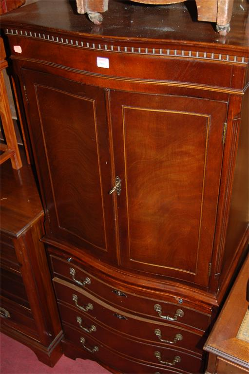 A reproduction mahogany serpentine front drinks cabinet