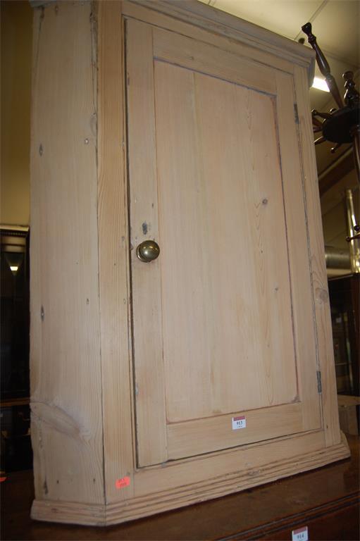 A 19th century single door hanging corner cupboard