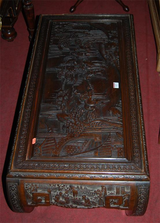 A Chinese hardwood low relief carved low occasional table on curved ends