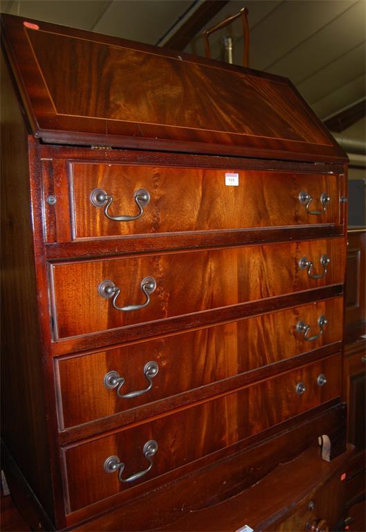 A reproduction mahogany slopefront four drawer writing bureau