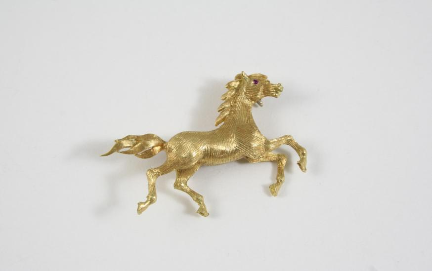 AN 18CT. GOLD HORSE BROOCH