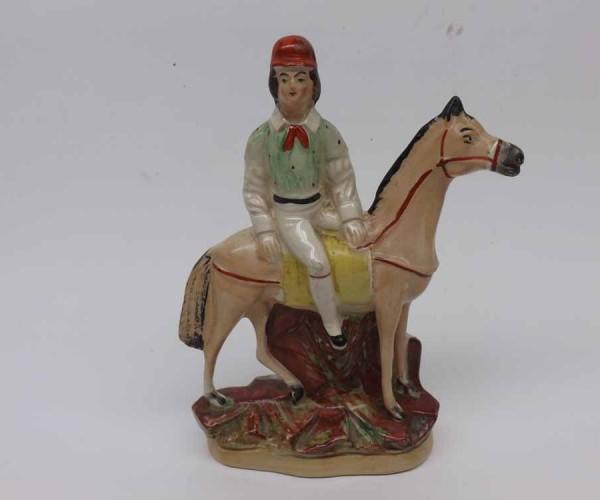 19th century Staffordshire model of jockey on horseback, raised on oval plinth base