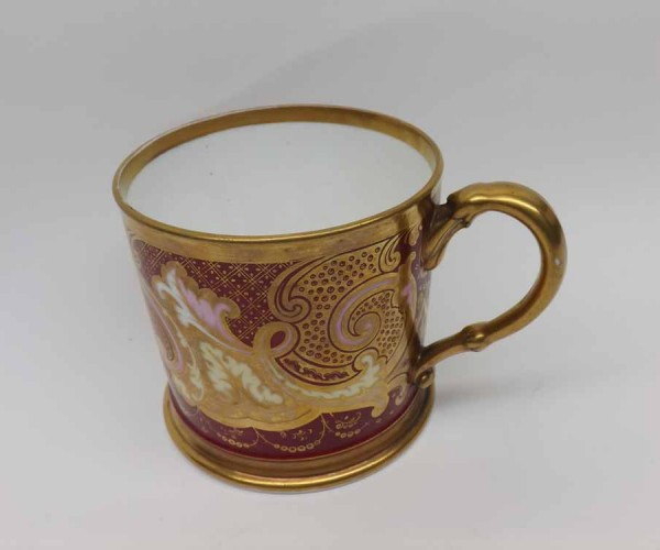19th century Staffordshire mug of circular form, the body decorated with gilt scroll detail on a red background