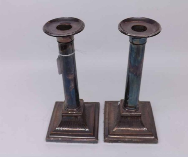 Pair of silver plated column formed candlesticks, with removable nozzles, raised on spreading square loaded bases