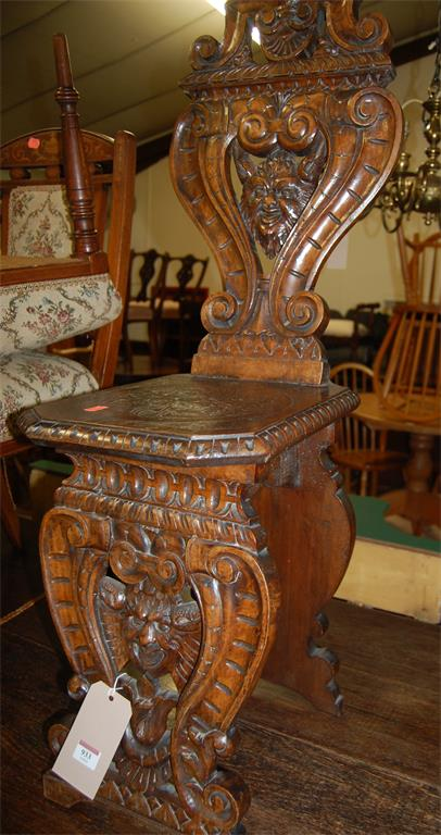 An antique Italian carved and pierced walnut panelled seat hall chair