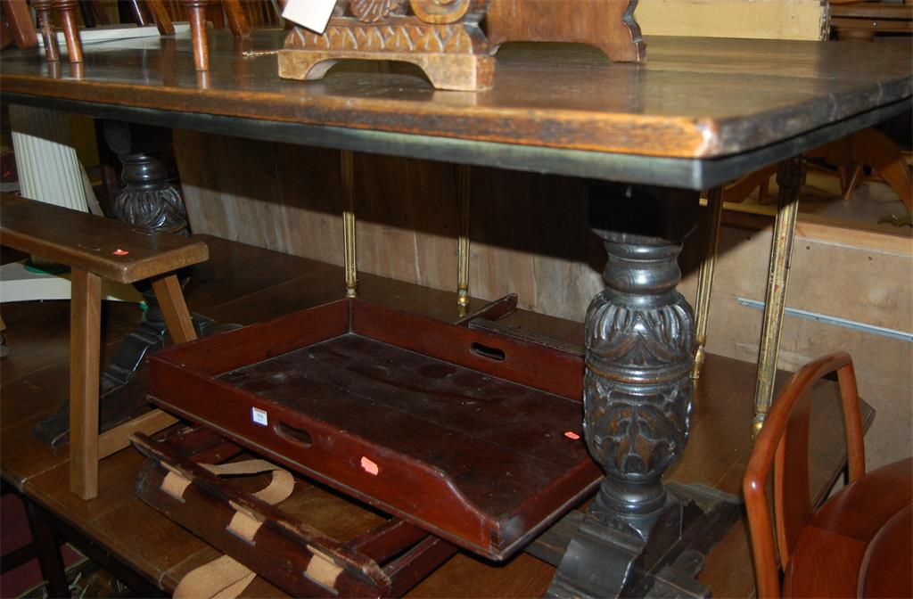 A 17th century style oak trestle end refectory table, raised on floral carved baluster supports
