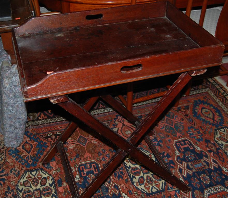 A 19th century stained oak twin handled butlers tray raised on folding stand