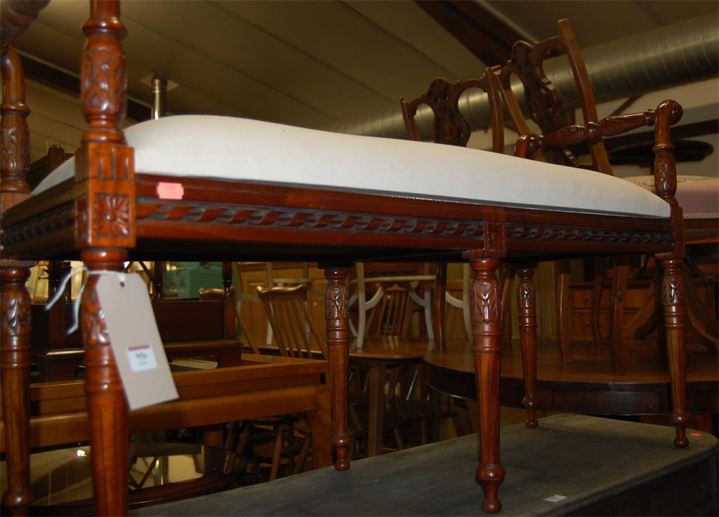 A reproduction mahogany twin window seat, having upholstered top and floral carved end carry handles
