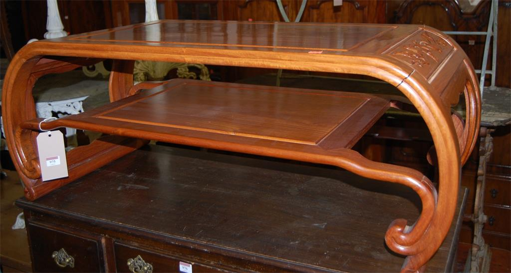 A contemporary Chinese hardwood two tier low occasional table, having curved ends