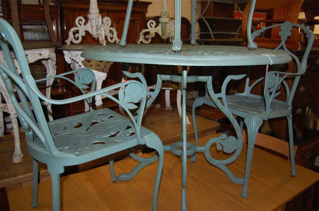 A Victorian style green painted cast metal circular garden table and four elbow chairs, with all-over pierced floral decoration