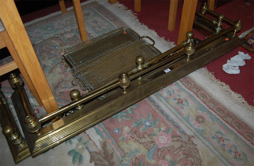 A late Victorian tubular brass curb fender; together with another similar; and a collection of fire screens