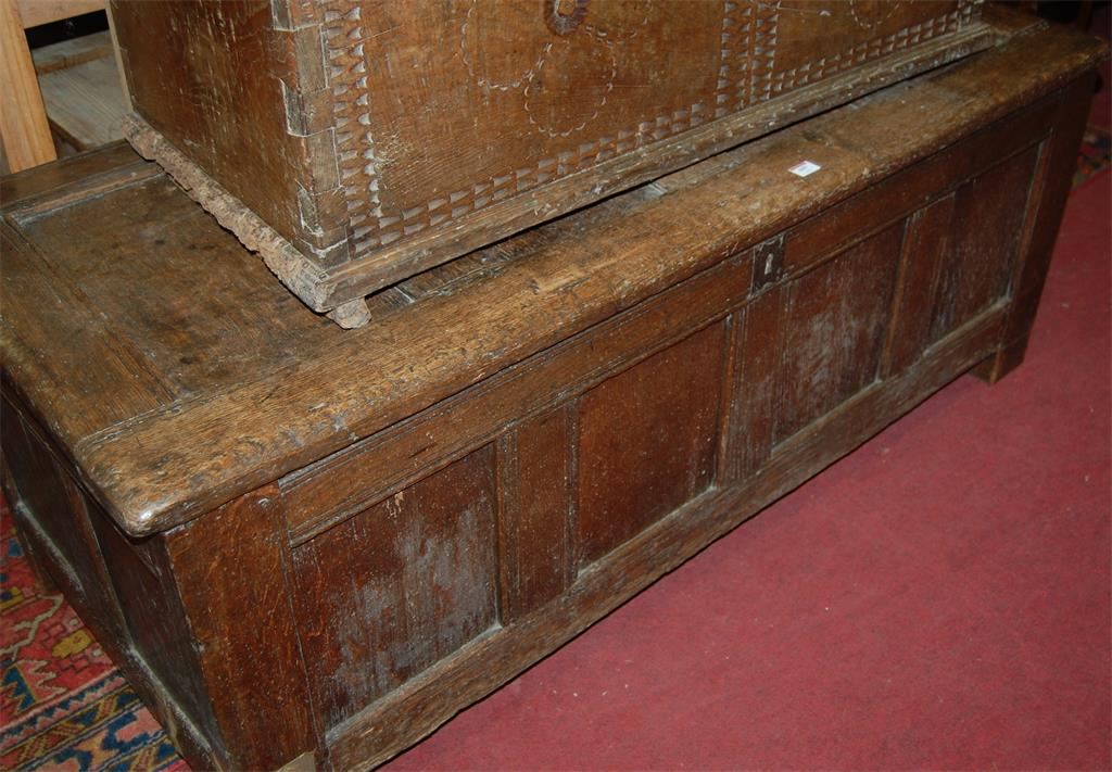 A circa 1700 joined oak four panelled hinge-top coffer
