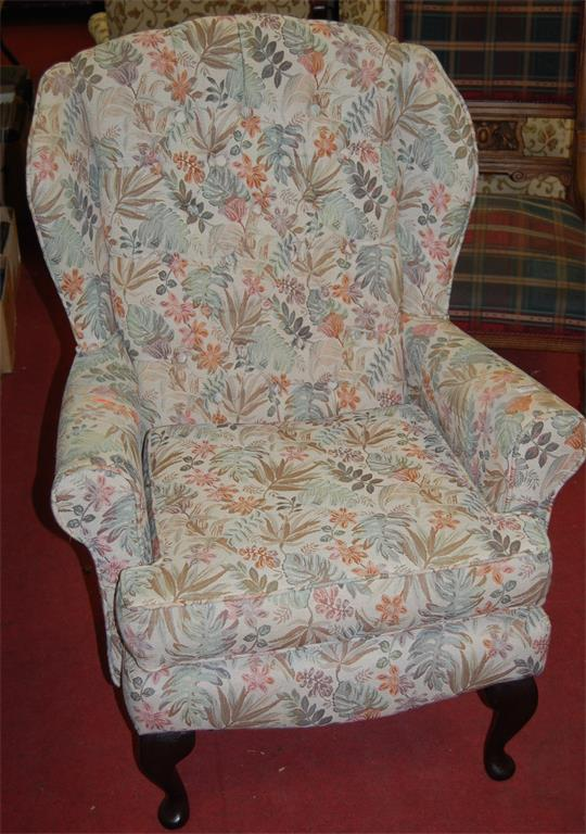 A modern floral upholstered buttonback wingback armchair