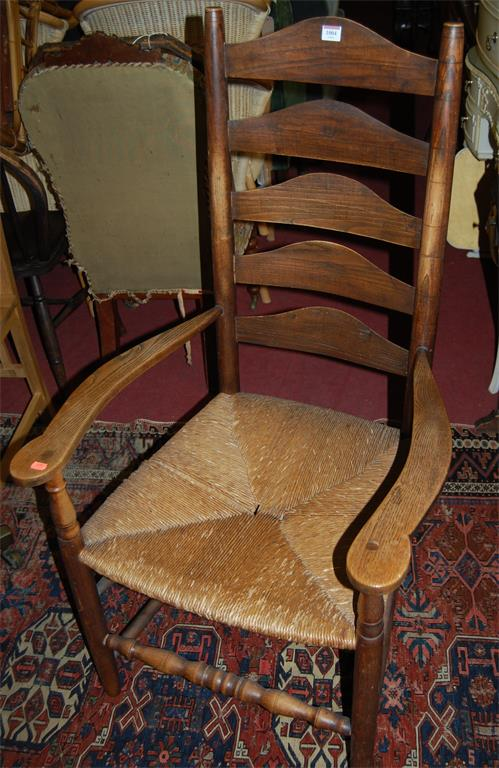 A circa 1900 oak and elm rushseat ladderback open armchair
