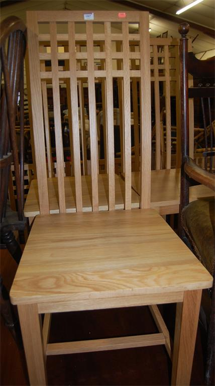 A contemporary set of six light oak panelled seat slatback dining chairs in the manner of MacIntosh