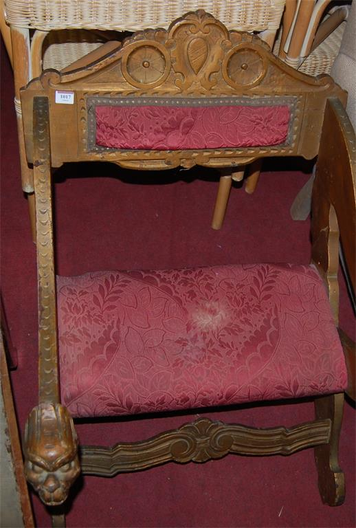 A circa 1900 carved and gilt painted, further red floral upholstered, X-framed armchair