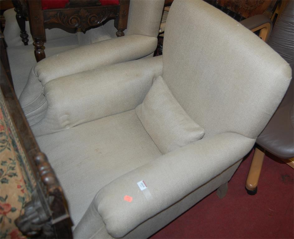 A pair of faded walnut framed and upholstered armchairs in the Howard style