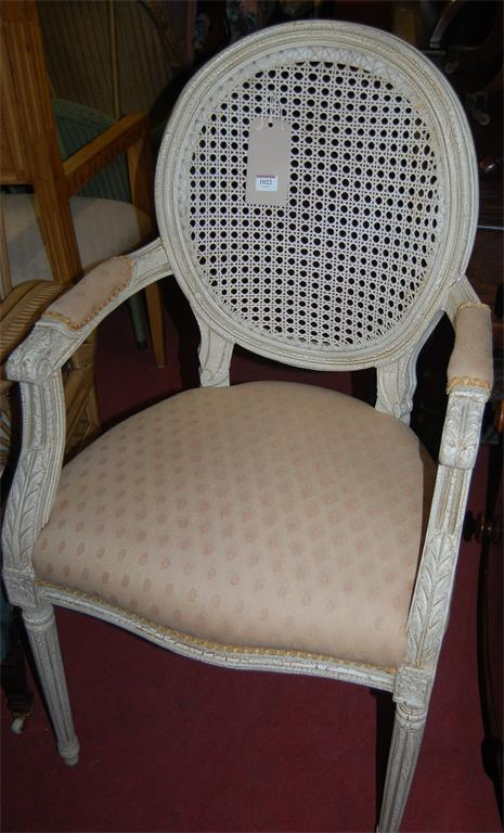 A Louis XVI style oak framed and cream upholstered fauteuil