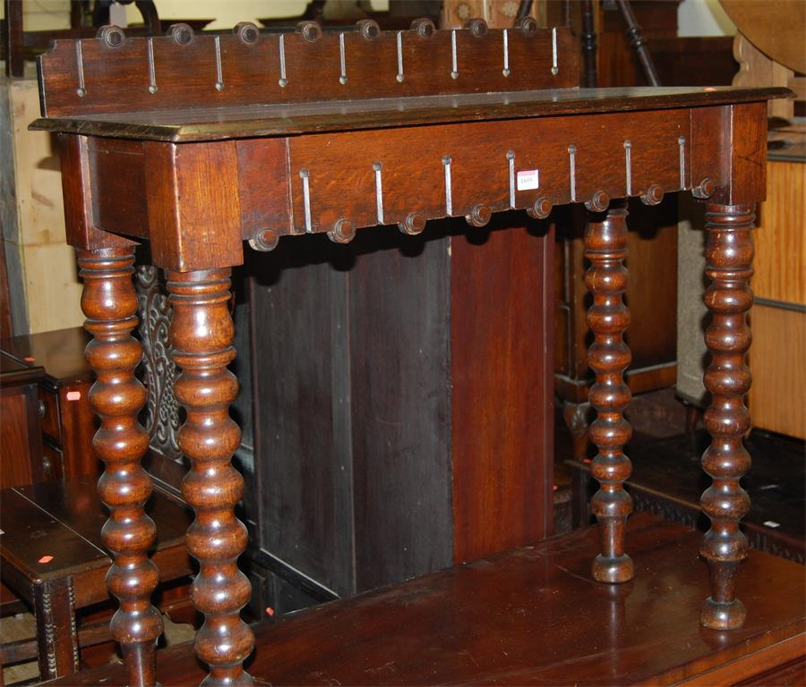 A late Victorian oak ledgeback hall table, raised on bobbin turned supports