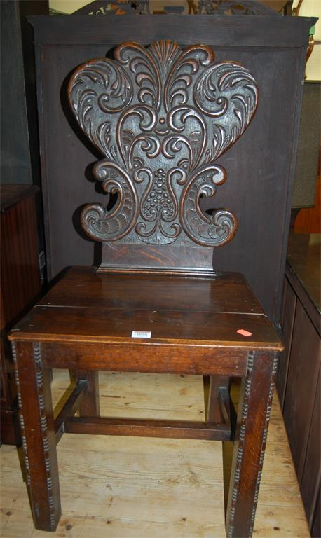 An early 20th century floral low relief carved oak and panelled seat hall chair