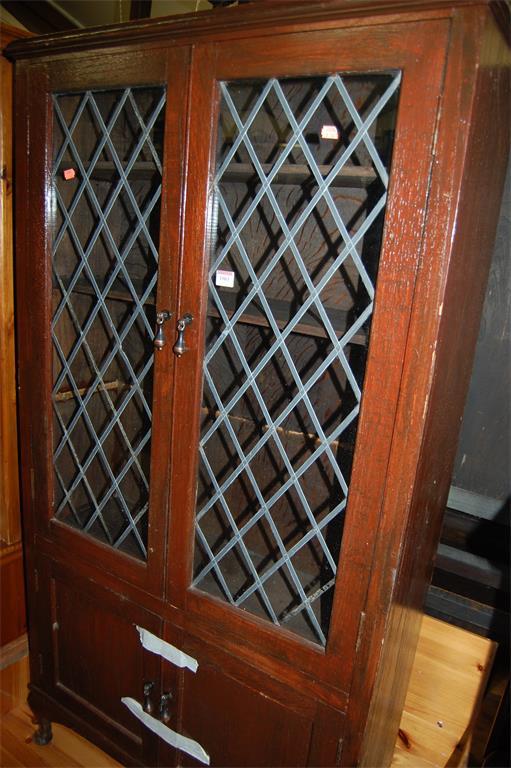 A 1930s stained oak double door lead glazed bookcase, having twin cupboard lower doors