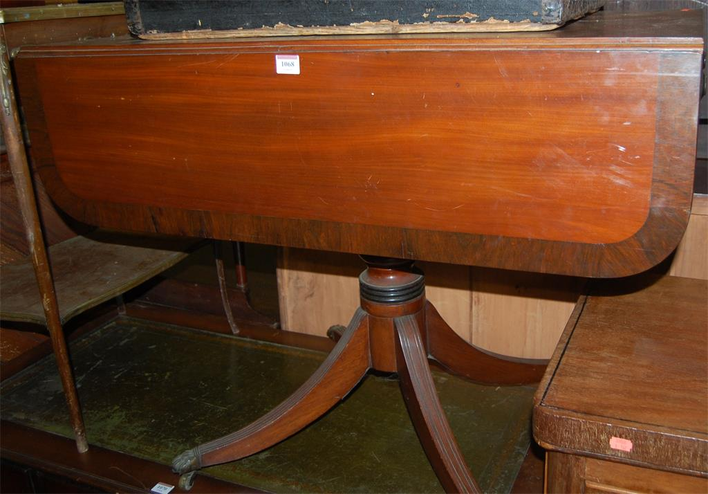 A circa 1830s mahogany and rosewood crossbanded round cornered dropflap pedestal supper table