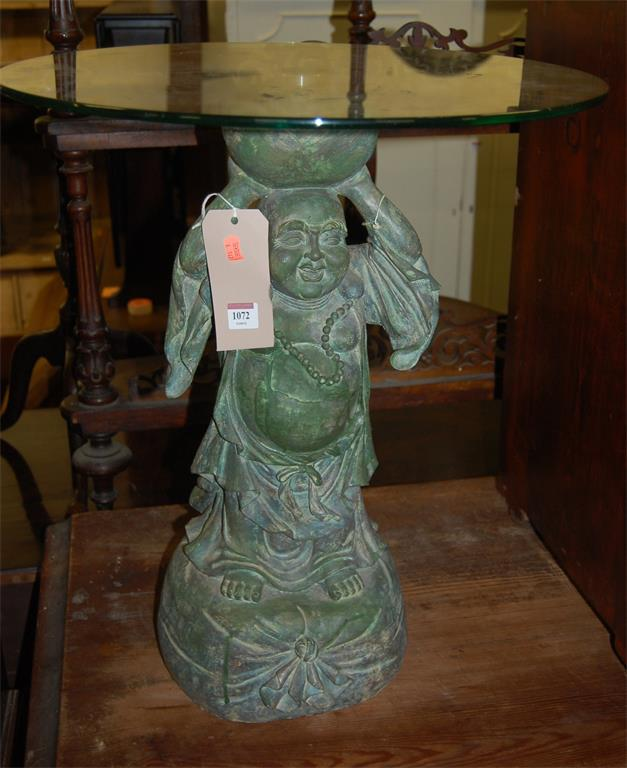 A circular glass topped occasional table, the base in the form of a standing Buddha